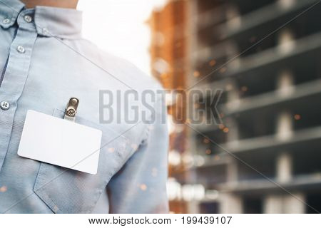 Blank White Blank Badge On Businessman's Shirt Close-up On Building Construction Background. Concept