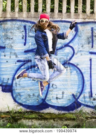 Cute young blonde teenager girl in a baseball cap and jeans shirt jumping against a stone wall background. Hip hop, dancing.