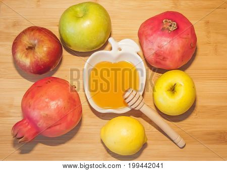 Fresh apples and pomegranates with sweet honey at the table during the traditional Jewish holiday Rosh HaShanah (Jewish New Year) concept.
