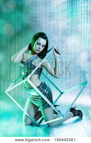 beautiful club girl with metal cube posing on silver background