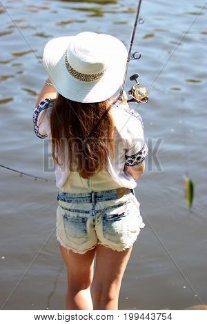 Young woman with sun hat while fishing on the river