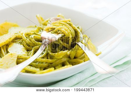 Closeup of linguine pasta with pesto genovese and potatoes over a table with cutlery