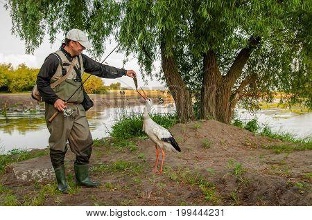 Fisherman Feeding Stork Bird By Fish On River Shore