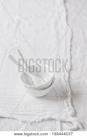 Two Porcelain Bowls and Teaspoons over White Cloth Background copy space for your text