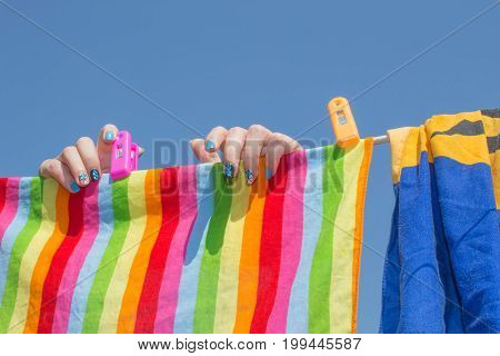 drying things hanging on a clothesline on a beautiful sunny day. Young woman hanging up laundry