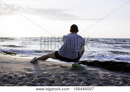 Sporty young man training on the beach, man with tattoo do exercises on the beach