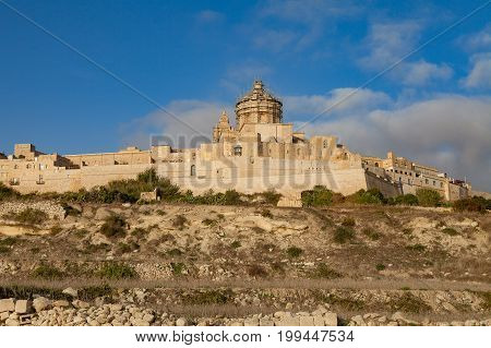 Ancient hilltop fortified by old capital city of Malta, The Silent City, Mdina or Rabat, skyline at sunrise.
