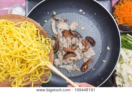 Chef putting Yakisoba noodle in pan / cooking Yakisoba (Fried Japanesed noodle) concept