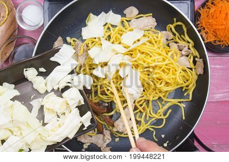 Chef put piece of cabbage for cooking Yakisoba noodle / cooking Yakisoba (Fried Japanese noodle) concept