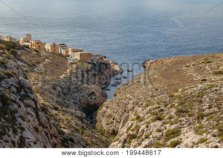 Limestone rocks covered by exotic plants - coast of Malta island. Small town on the rock