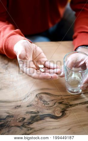 Medical pill on the wrinkly hand of an old man.