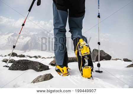 caucasian mans walking with crampons and Stick for Nordic walking