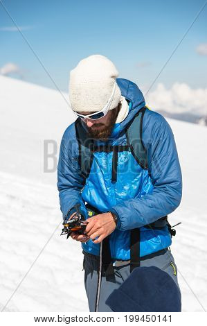 A young guide with a beard and sunglasses prepares crampons for use