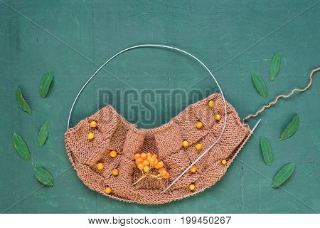 Autumnal knitting with leaves and ashberries on green background shot overhead.