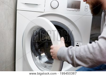 Young men is prepering clothes for washing.