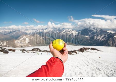 A man's hand holds an apple against the background of snow-capped mountains and snow underfoot. The concept of chilled fresh food and snack