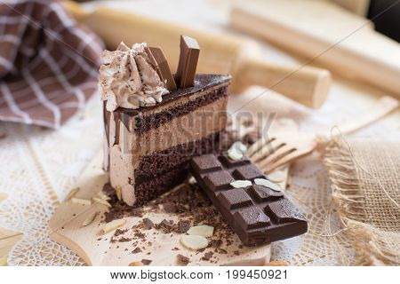 Chocolate Cake Slice With Chocolate Cream And Chocolate Bar. Cake Background Concept