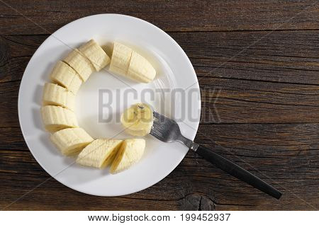 Sliced bananas in plate and fork on dark wooden table top view