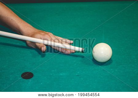 A man playing snooker at a emerald table, aiming. Focus on a white ball