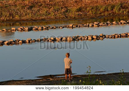 An unidentified boy is fishing in a homemade drainage diversion ditch.