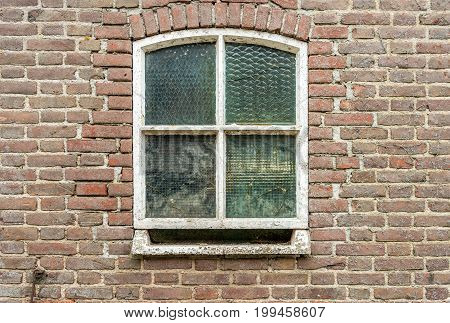 Closeup of and old and weathered window with reinforced glass in a restored masonry wall with cracks.