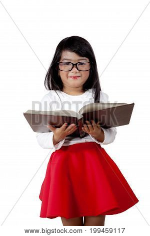 Portrait of a little adorable girl reading a book while smiling at the camera isolated on white background