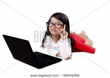 Picture of adorable girl thinking an idea while using a laptop computer isolated on white background
