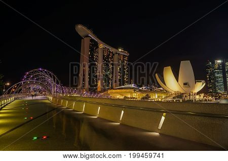SINGAPORE - JUNE 17 2014 : Bridge to Marina Bay Sands Hotel at night in Singapore