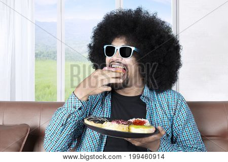 Photo of Afro person with curly hair eating a plate of delicious donuts while wearing sun glasses at home