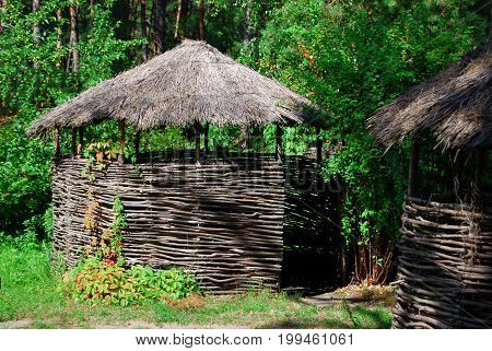 Arbor of woven branches with thatched roof