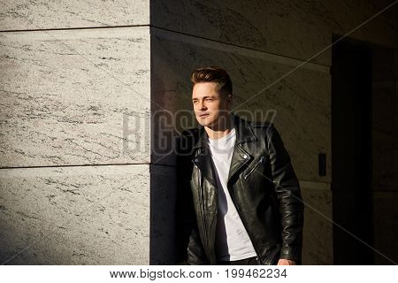 Lifestyle picture of fashionable cool smooth-shaven young Caucasian male dressed in trendy black leather jacket over white t-shirt standing outdoors leaning shoulder on wall waiting for someone