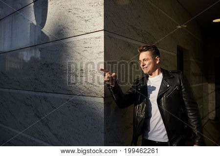 Urban portrait of trendy-looking young man wearing stylish leather jacket looking in front of him and pointing index finger after he came across a friend on streethaving cheerful excited look