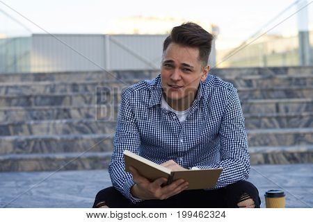Outdoor picture of attractive European male student sitting on concrete stairs outside university building holding copybook revising new words before Spanish lesson. People and urban lifestyle