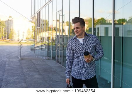 Enjoying city lifestyle. Handsome young man in casual wear standing on street with coffee-to-go in paper cup carrying bag looking away with positive cheerful facial expression going home from office