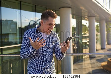 Human emotions and reaction. Cheerful excited young employee standing outside office buidling during working day watching footbal game online via social media screaming while supporting local team