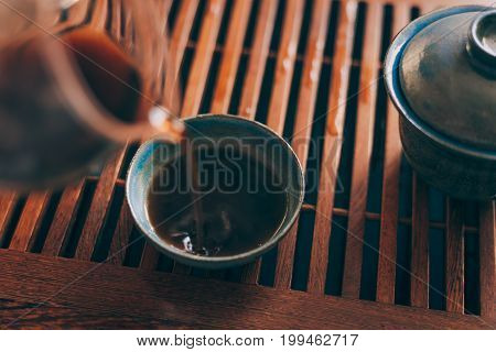 Chinese tea cup is poured by hot fresh black tea of Shu Puer or Puerh on Chinese tea board, selective focus