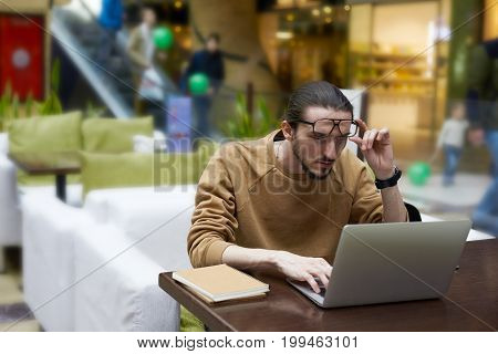 Unshaven male student taking off his glasses and staring at laptop screen with focused look sitting at cafe table with textbooks doing homework looking for information for course paper on internet