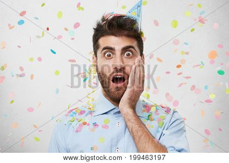 Attractive Bearded Man With Surprised Expression, Keeping His Hand On Cheek, Wearing Shirt And Party