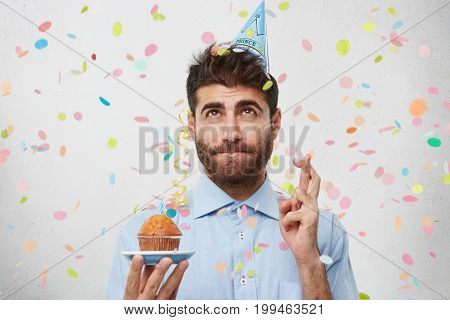 Handsome Guy In Holiday Cap And Formal Shirt, Holding Birthday Cupcake In Hand, Crossing His Fingers