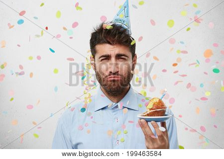 Headshot Of Sad Disappointed Man Wearing Cone Hat On His Hand, Posing At Studio Wall With Confetti F