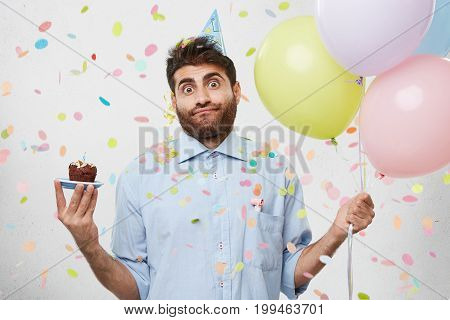 Confused Puzzled Young Man With Stubble Standing At White Wall With Balloons And Cake In His Hands,
