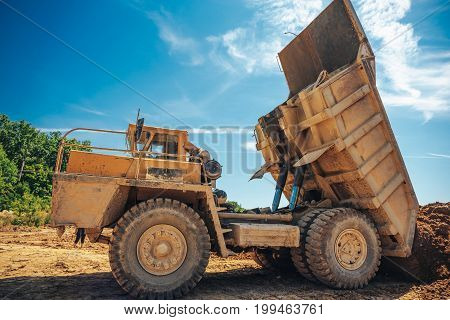large industrial yellow truck unload process, the truck works on a quarry mining