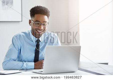 Indoor Office Shot Of Cheerful Successful Young African American Manager With Stubble Sitting In Fro