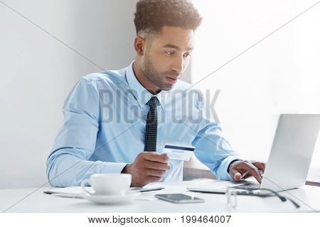 Indoor Shot Of Black Male Businessman Wearing Blue Shirt With Tie Using Laptop Computer In Office Ho