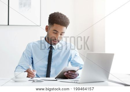 Busy Mixed Race Businessman, Wearing Formal Clothes, Writing In His Pocketbook And Holding Electroni