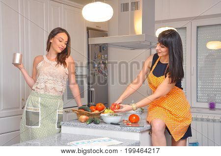 Mature mother and daughter cooking together in the kitchen. Happy family spend time in kitchen