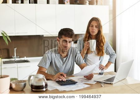 Candid Shot Of Young American Couple Managing Family Budget, Reviewing Bank Accounts Using Laptop An