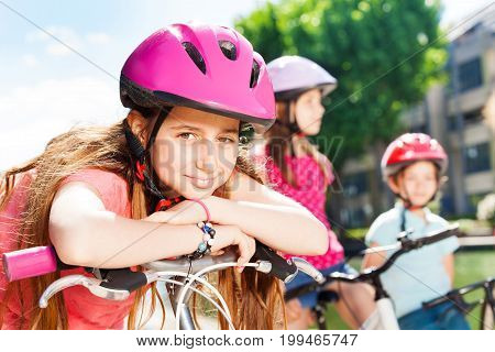 Portrait of beautiful preteen girl in pink safety helmet having rest during bicycle ride with friends