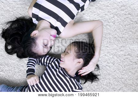 Top view of a beautiful woman looking at her daughter while lying down on the carpet