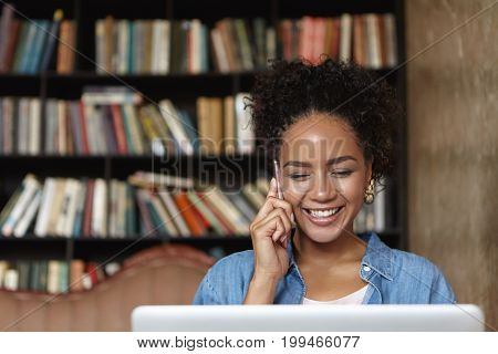 Beautiful Student Girl With Charming Smile Talking On Mobile Phone While Studying At College Library